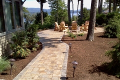 After picture of paver patio and fire pit installed in New Hampshire's Lakes Region Landscape lighting was installed by the homeowners